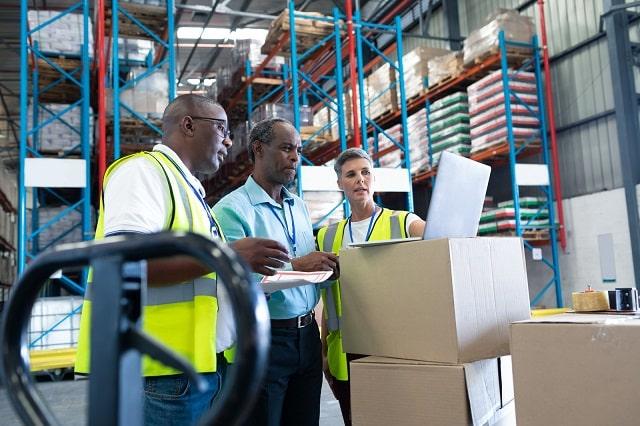 Warehouse workers reviewing warehousing KPIs on laptop