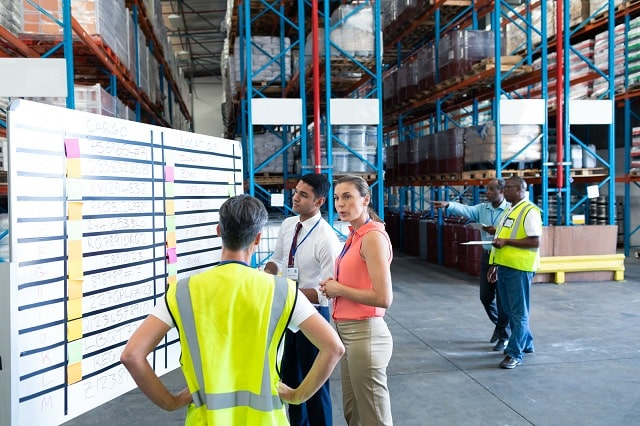 Warehouse workers discussing warehousing KPIs