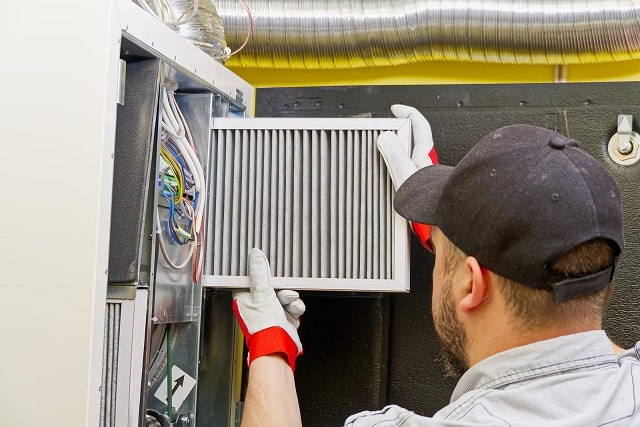 Technician replacing air filter in HVAC unit
