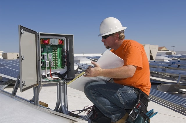 Electrician performing maintenance on electrical box at solar plant