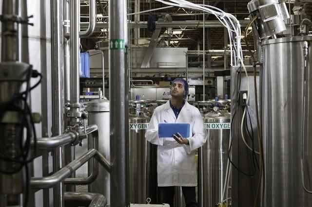 Factory maintenance worker checking bottling equipment